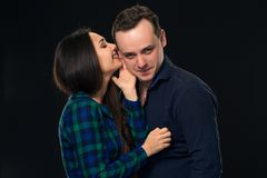 Woman whispering into a man`s ear. On black background stock photo