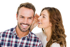 Woman whispering into mans ears Stock Photo