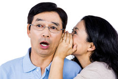 Woman whispering into partners ear Stock Images