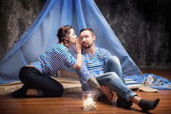Woman whispering rumors in the ear of a man. Wigwam background Stock Photo