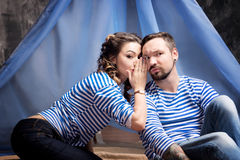 Woman whispering rumors in the ear of a man. Wigwam background Royalty Free Stock Photos