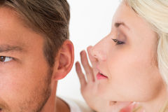 Woman whispering secret into a mans ear. Close up of a women whispering secret into a mans ear over white background stock photo
