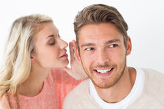 Woman whispering secret into a mans ear. Close up of a women whispering secret into a mans ear over white background stock photos