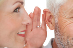 Woman whispering secret into a mans ear Stock Photos