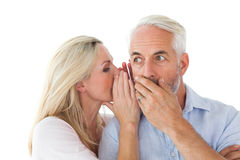 Woman whispering a secret to husband Stock Photo