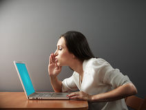 Woman whispering secrets to her laptop Stock Photography