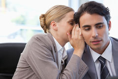 Woman whispering something to her colleague Royalty Free Stock Photos