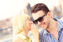 Woman whispering to boyfriend. A picture of a women whispering to boyfriend Royalty Free Stock Images