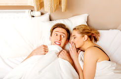 Woman whispering to her husband and he laughting.  Stock Photography