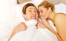 Woman whispering to her husband and he laughting.  Stock Image