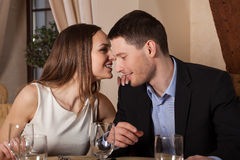 Woman whispering to her man Stock Photography