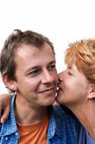 Woman whispering to man. A middle aged woman whispering to a man's ear Stock Image
