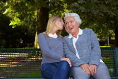 Woman whispering to senior woman Stock Image