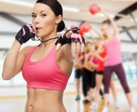 Woman with whistle in gym. Fitness, sport, training, gym and lifestyle concept - beautiful sporty women with whistle in gym Stock Images