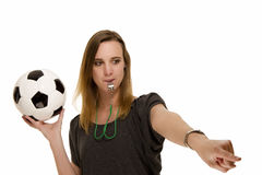 Woman with a whistle holding a football pointing a Stock Images