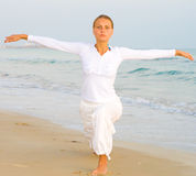 Woman in white. Dress practising yoga Stock Images