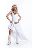 Woman In White. Young blonde woman in a white dress and cowboy boots stock image
