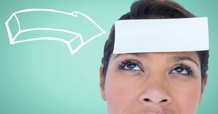 Woman with white arrow pointing to card on head against aqua background Stock Photo