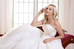 Woman in white ball gown sitting on red fainting couch. Portrait of woman in white ball gown sitting on red fainting couch Royalty Free Stock Photography