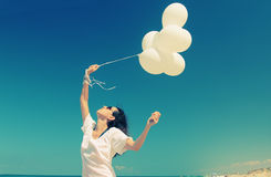 Woman with white balloons Stock Images