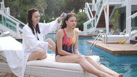 Woman in white Bathrobe brushing her daughter`s hair sitting on a lounge chair by the pool at the Villa. stock footage