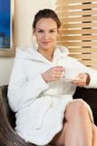Woman in white bathrobe sitting and holding cup of tea Royalty Free Stock Images