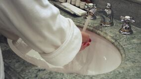Woman in white bathrobe turning water faucet and washing hands. In bathroom sink. Close up female hands opening water tap and washing hands in bath room stock video