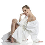 Woman in white bathrobe. Very beautiful woman dressed in a white bathrobe in wellness style royalty free stock image