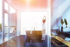 Woman in white bathroom with balcony. Woman in pajamas standing in luxury bathroom with black marble floor, black bathtub and double sink. Toned image royalty free stock images