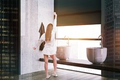 Woman in white bathroom corner. Rear view of woman in pajamas standing in luxury bathroom corner with concrete and gray walls, wooden floor, loft window and two stock images