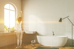 Woman in white bathroom corner, white tub. Woman in pajamas in white wall bathroom corner with wooden floor, arched windows, white bathtub, and double sink royalty free stock photo