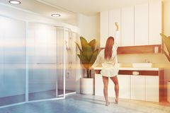 Woman in white bathroom, double sink and shower. Woman in corner of modern bathroom with white walls, concrete floor, double sink standing on white and wooden royalty free stock photography