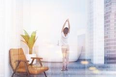 Woman in white bathroom interior, armchair stock photos