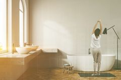Woman in white bathroom interior, white tub. Woman in pajamas in white wall bathroom interior with wooden floor, arched windows, white bathtub, and double sink stock photos