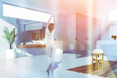 Woman in white bathroom with sink. Woman in corner of modern bathroom with white walls, concrete and wooden floor, white sink standing on white and wooden royalty free stock photography