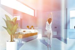 Woman in white bathroom with sink and toilets stock photography