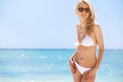 Woman in white bikini on the beach Stock Photos