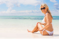 Woman in white bikini enjoying summer day at the beach stock photography