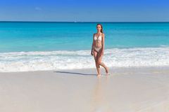 Woman in white bikini goes to bathe in waves of the Caribbean Sea Stock Images