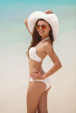 Woman in a white bikini and hat on a tropical beach. Royalty Free Stock Photography