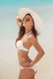 Woman in a white bikini and hat on a tropical beach. Royalty Free Stock Photos