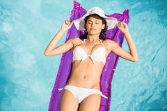 Woman in white bikini lying on air bed in po Royalty Free Stock Images