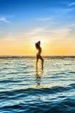 Woman in white bikini posing in a sea Stock Image