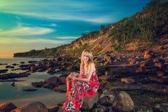 Woman in white bikini posing in a sea at sunset Stock Photos