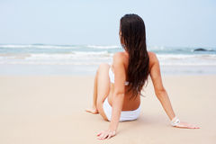 Woman in white bikini sitting at the beach Stock Photos