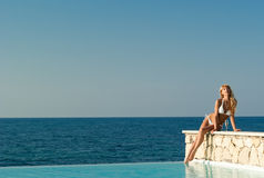 Woman in white bikini sitting on the edge of pool Stock Photos