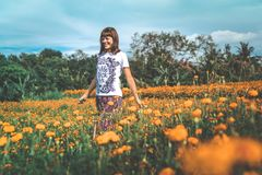 Woman in White and Black Floral Crew-neck T-shirt and Red Bottoms Standing on Orange Petaled Flower Field at Daytime royalty free stock image