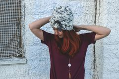 Woman in White and Black Knit Cap Posing Near White Wall Royalty Free Stock Images