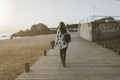 Woman in White and Black Long Sleeve Shirt and Black Pants Carrying a Black Bag Walking Brown Wooden Pathway Royalty Free Stock Photos