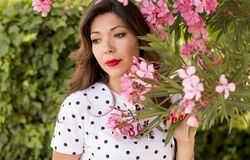 Woman in White and Black Polka Dots Dress Near Pink Flowers during Daylight Royalty Free Stock Photos